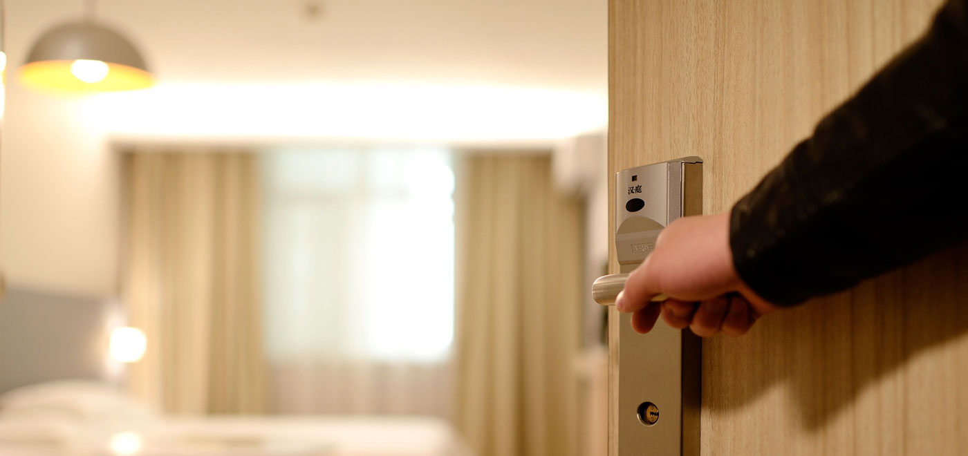 A person opens the door of his comfortable hotel room