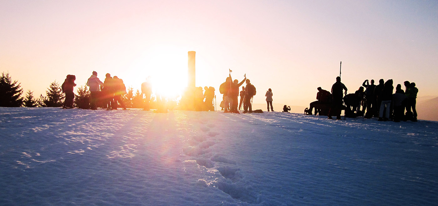 friends talking on the snow after skiing at sunset
