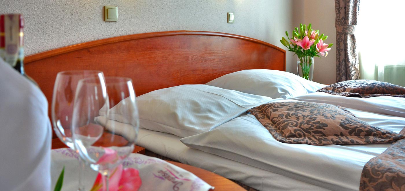 A beautiful double bed in a hotel room with a flower pot on the bedside table