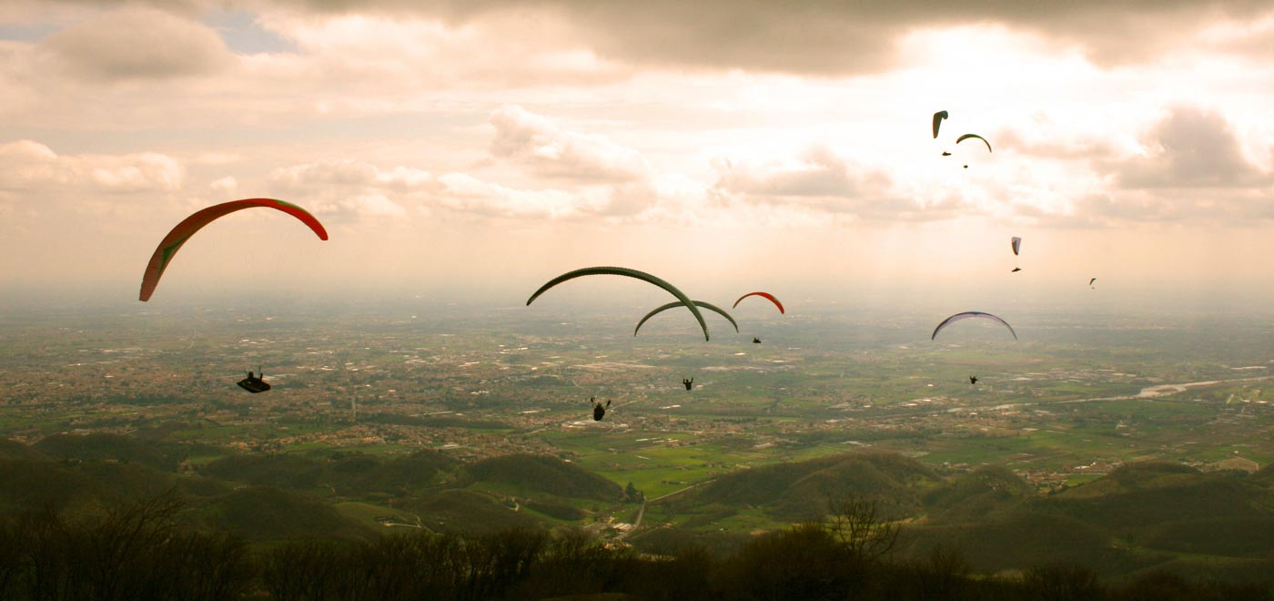 Some people paragliding in the sky around Monte Grappa